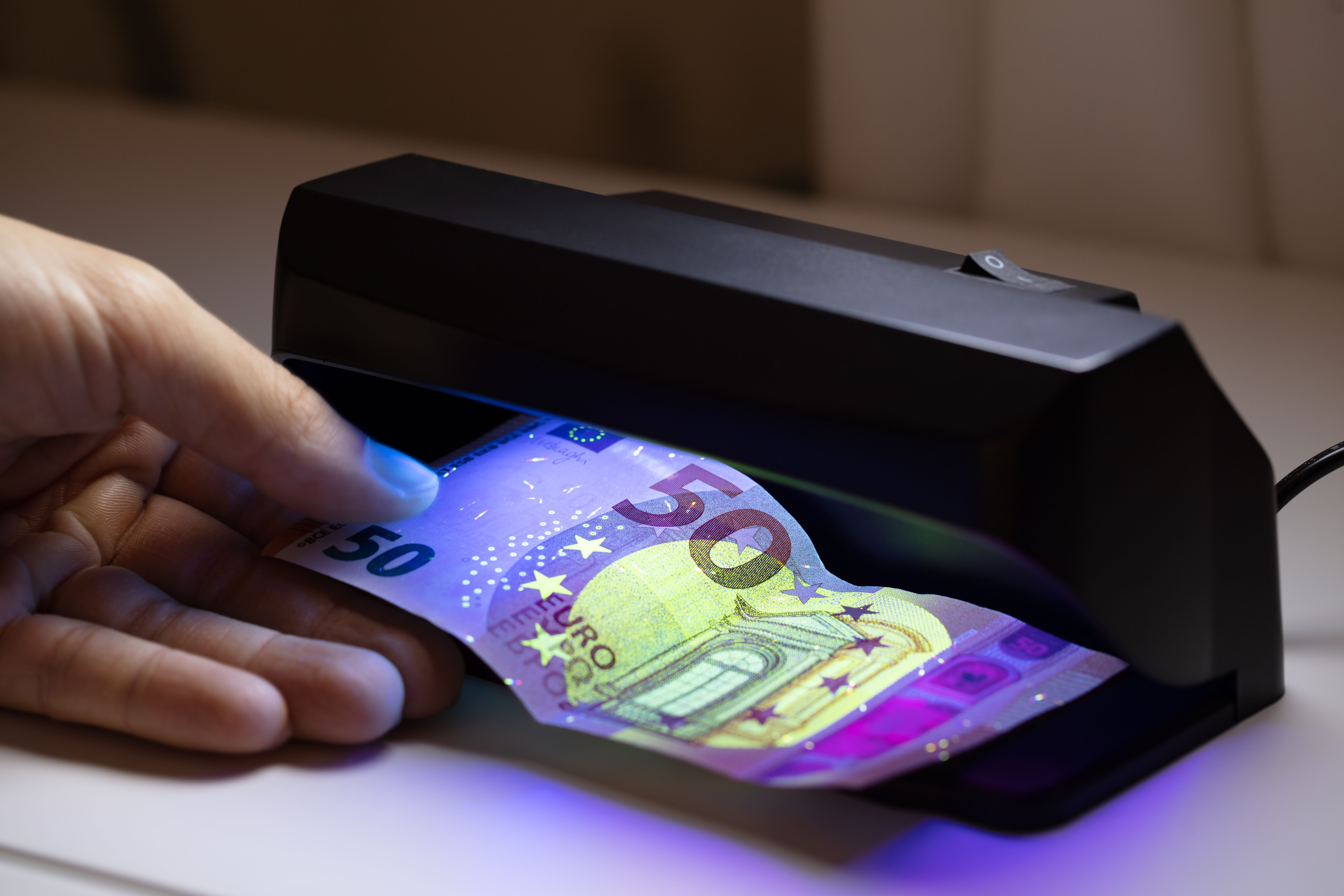 Close-up,Of,Man,Hand,Checking,Bank,Note,Through,Currency,Detector.jpg
