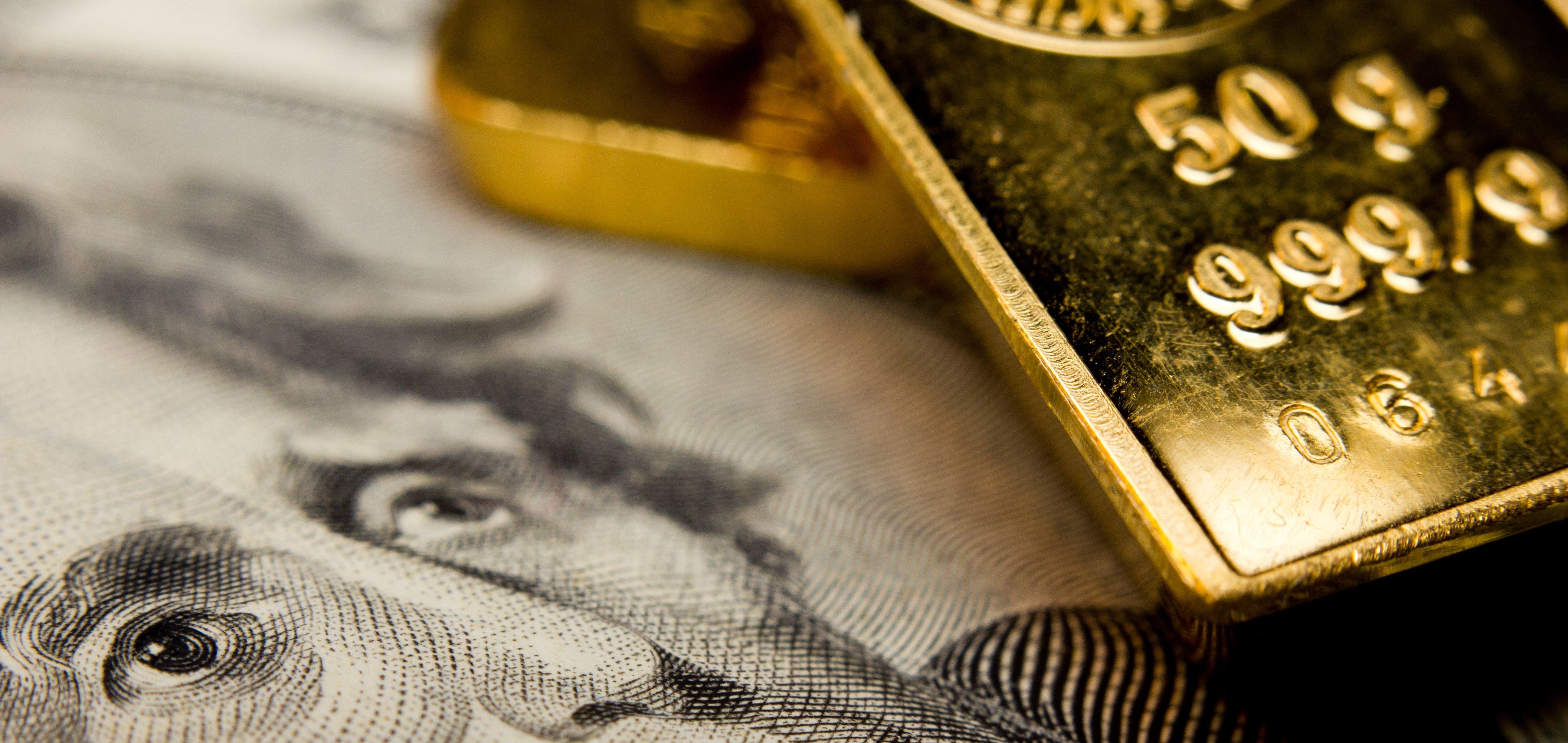 lingote de oro, oro de inversión y billete de dólar